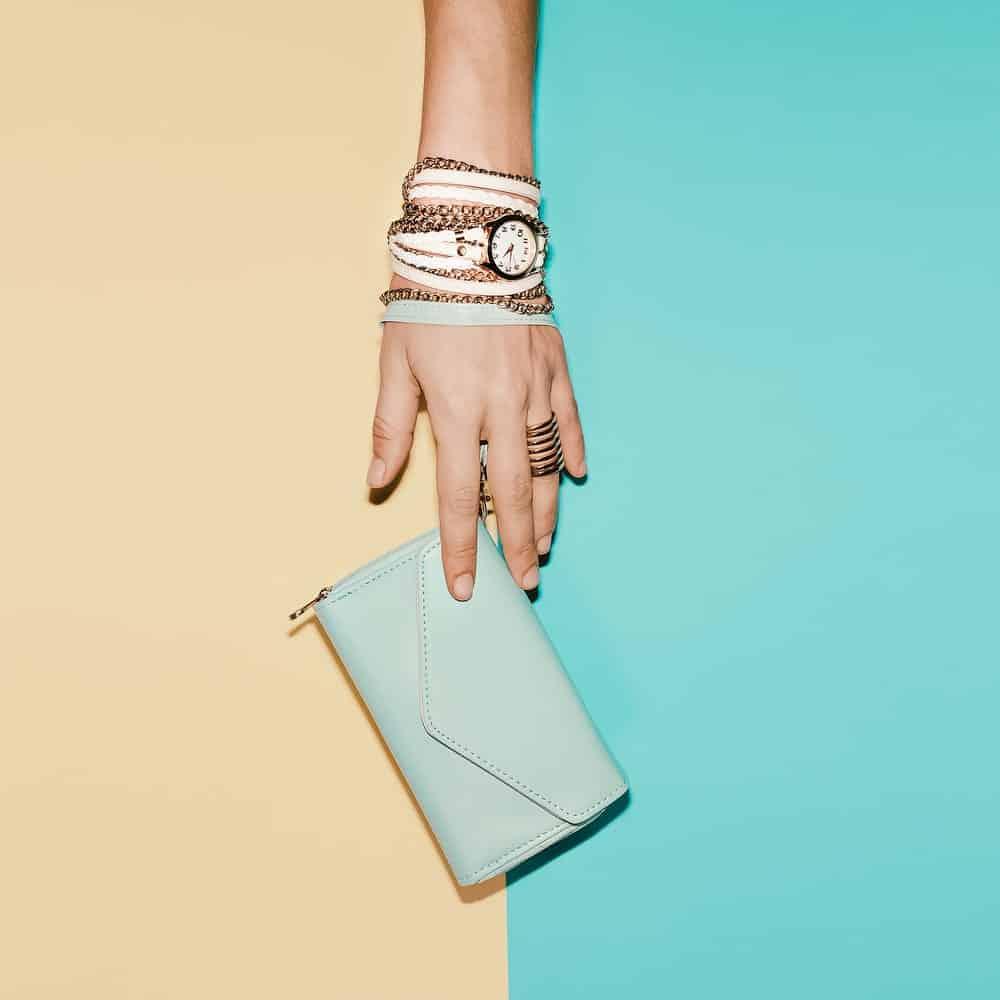Hand wearing watch, bracelets, and wristlets.