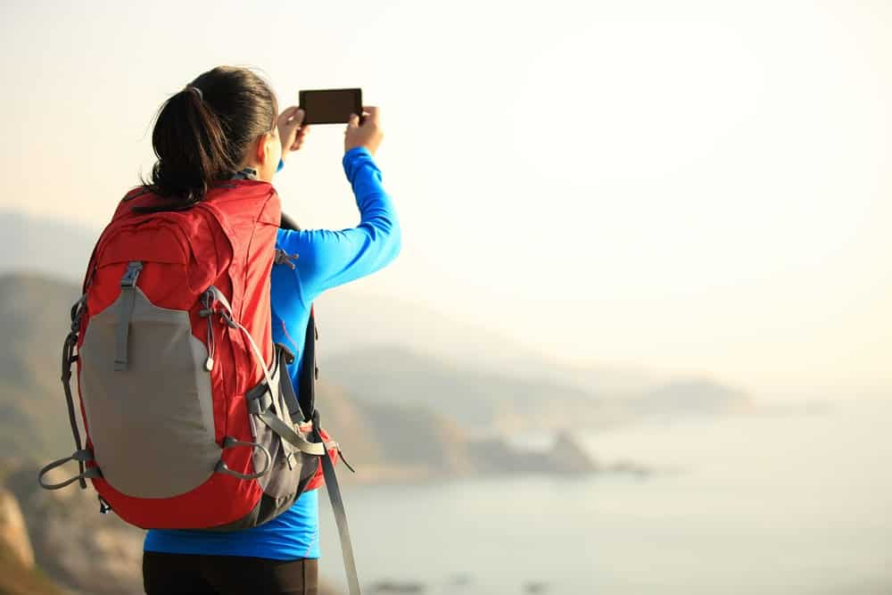 Woman with a red backpack taking a photo on top of the mountain.