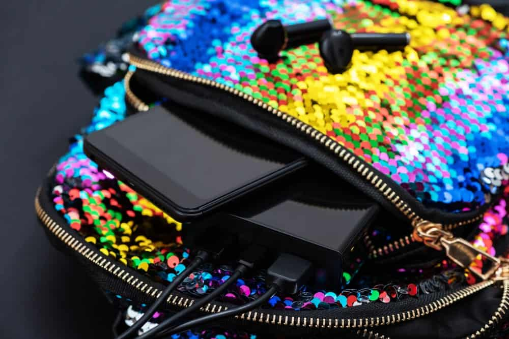 Smartphone and powerbank inside the multicolored sequined backpack.
