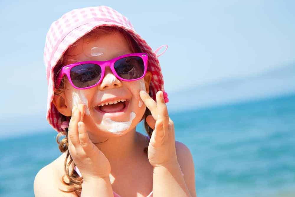 A kid wearing a beach hat at the beach.