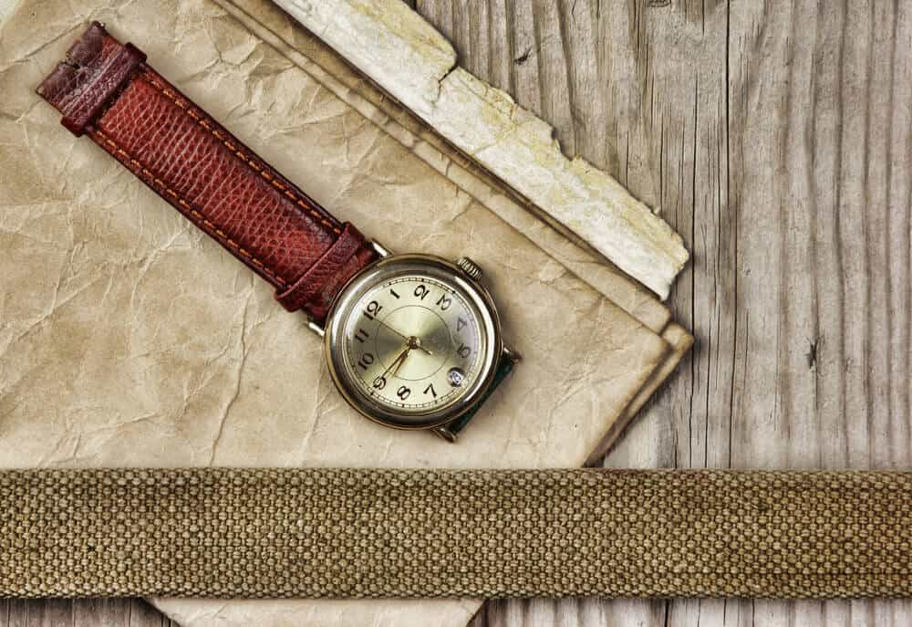 A broken wristwatch on vintage papers and wooden background.