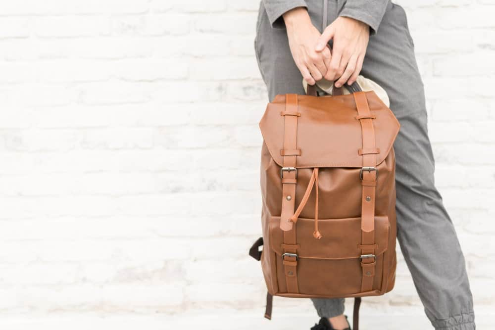 Man carrying a brown leather backpack.