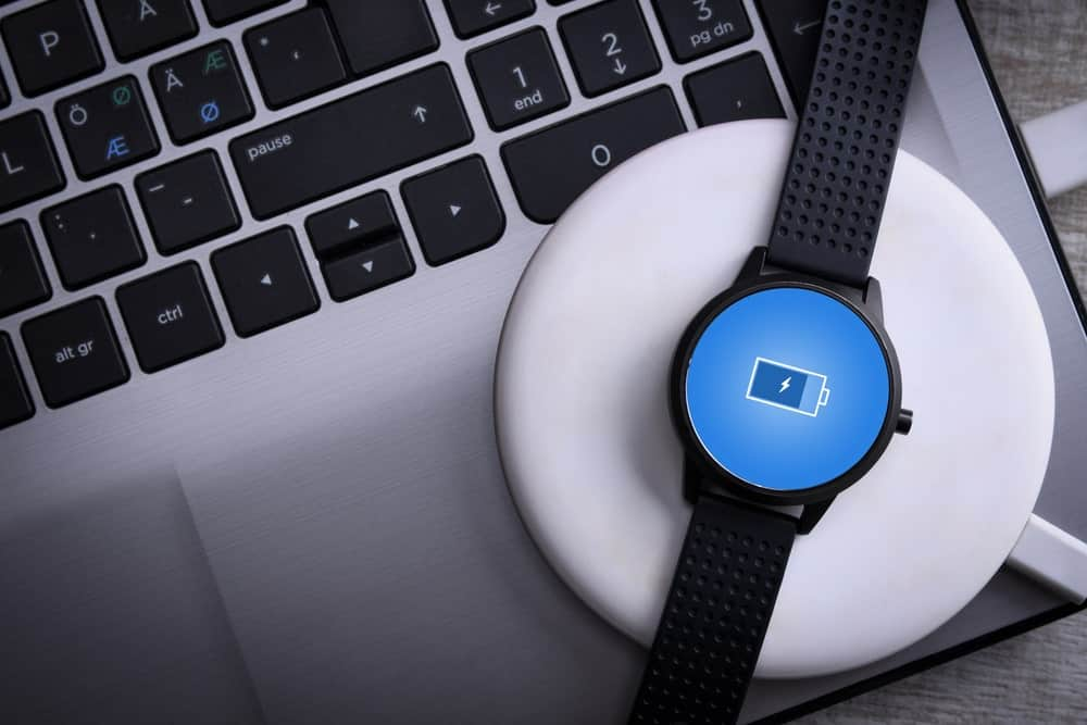 A smartwatch being charged on a wireless charging platform.