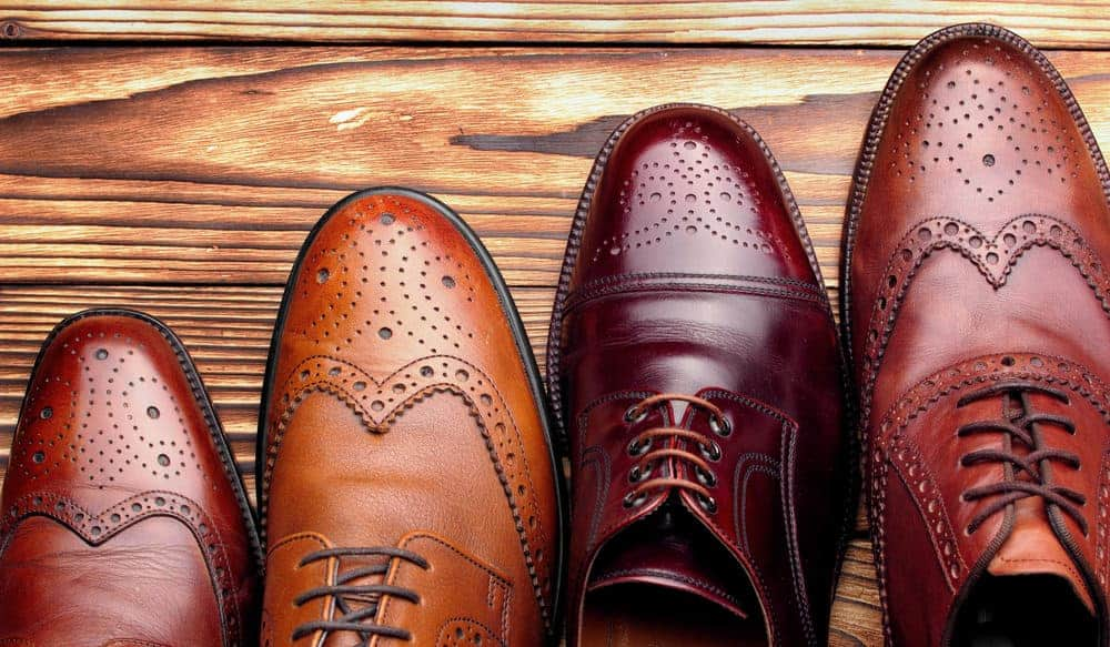 A variety of formal dress shoes on a wooden surface.