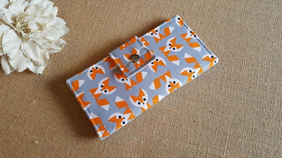 Gray fabric wallet with printed fox cartoons.