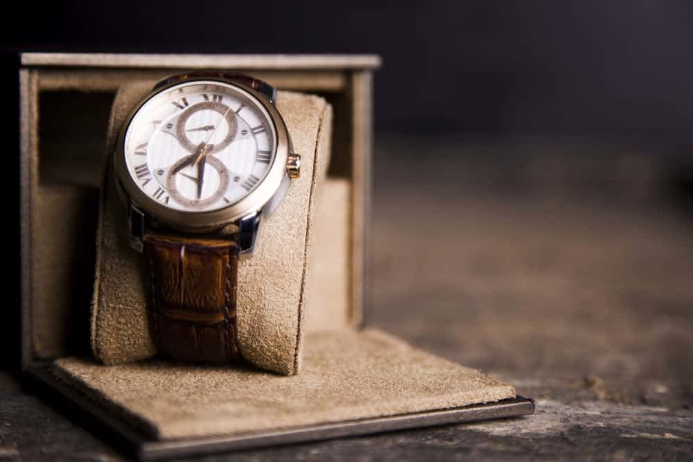 A watch with leather straps stored on its case.
