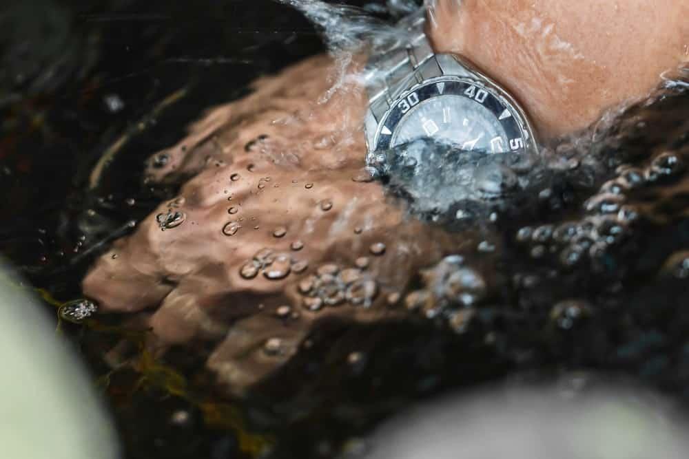 A hand wearing a watch splashing underwater.