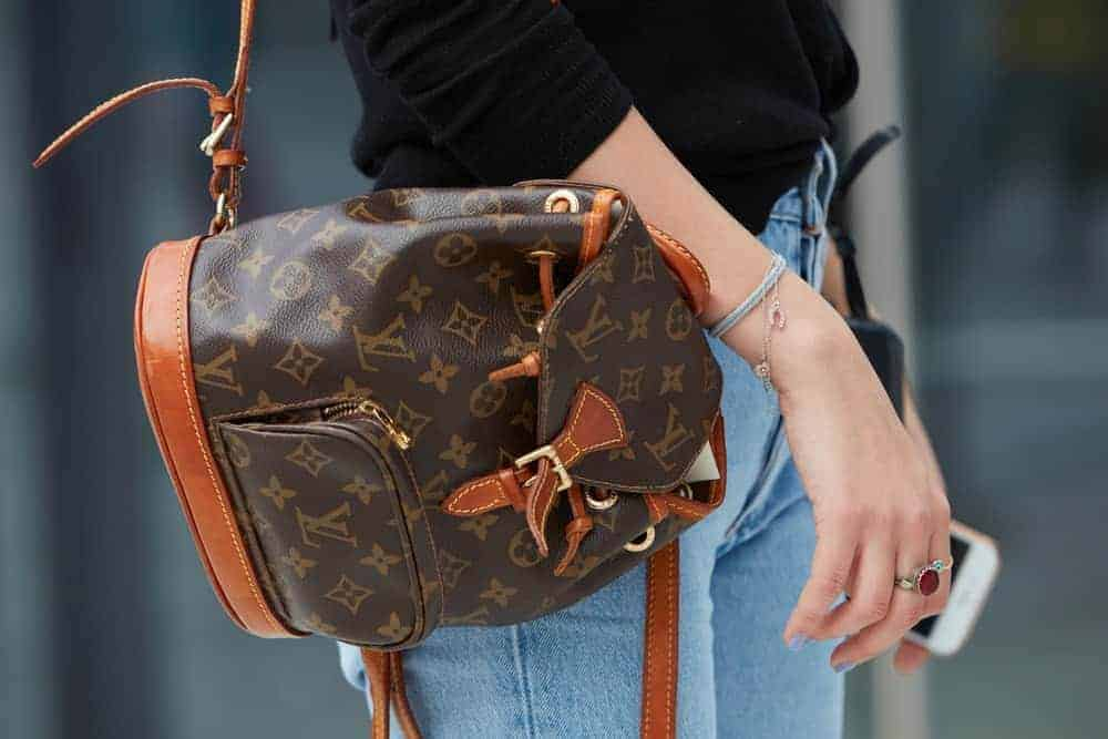 A close look at a woman carrying a Louis Vuitton backpack.