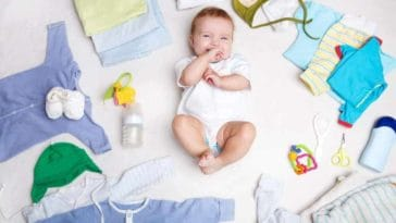 A baby surrounded with various baby clothes.
