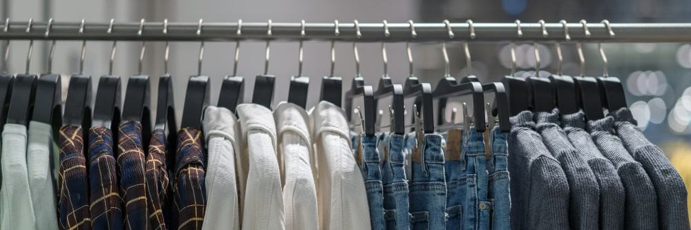 Clothes rack display filled with men's garments.