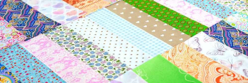 Lots of multi-colored cotton fabric laid out in a diagonal form.