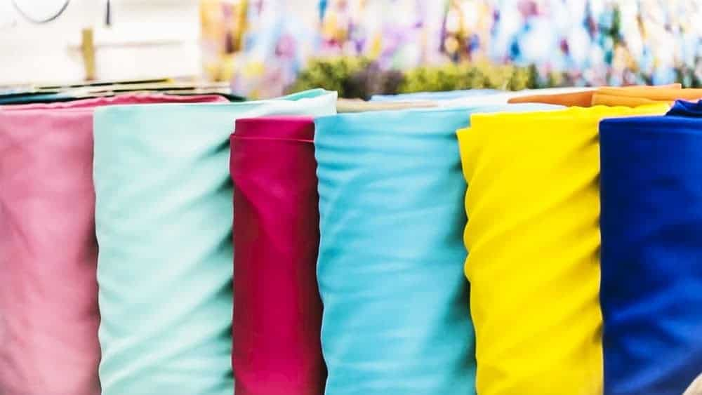 Stacks of colorful textiles in a fabric store.