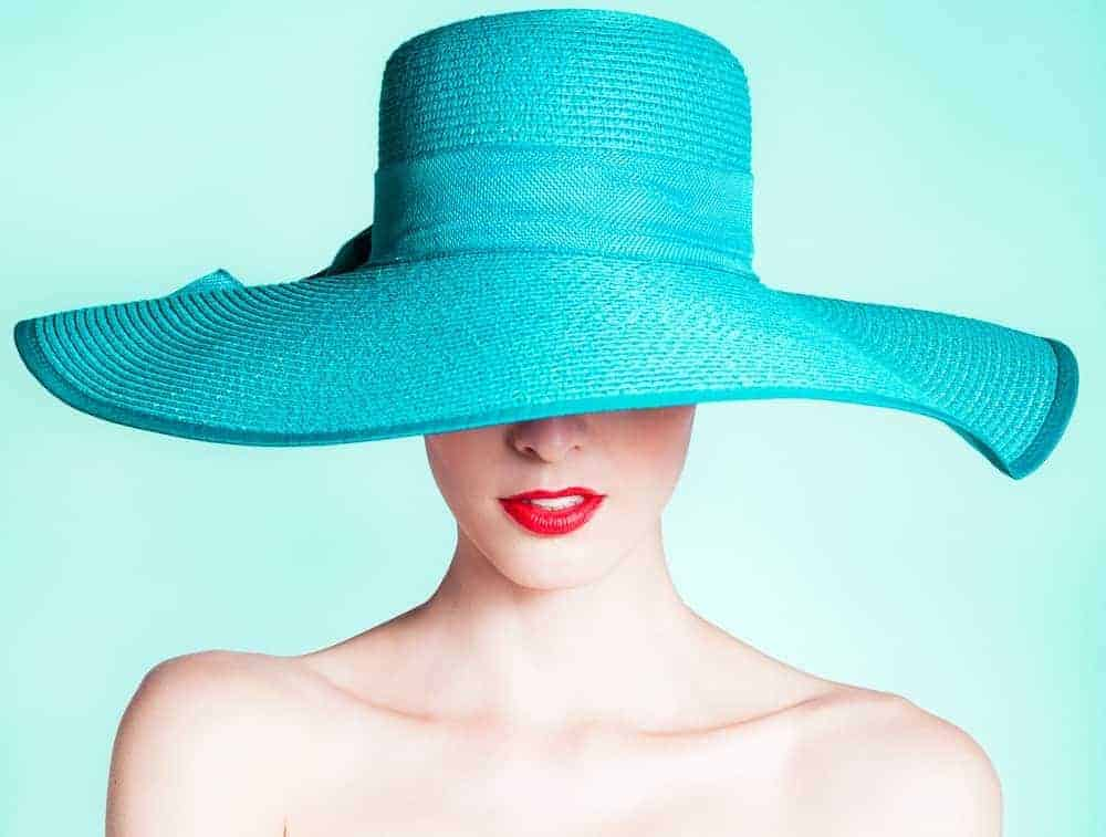 A woman wearing an aquamarine wide-brimmed hat.