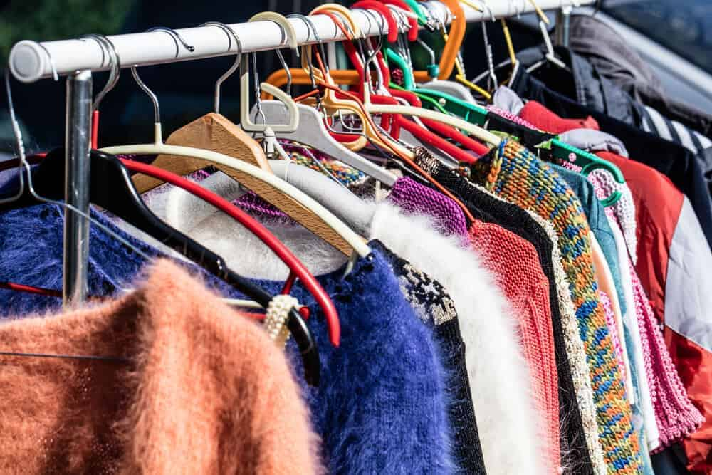 Second hand clothing of different styles and colors on display.