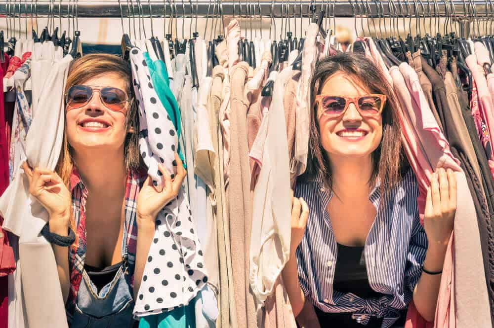 A couple of women having fun at the rack of vintage clothes.