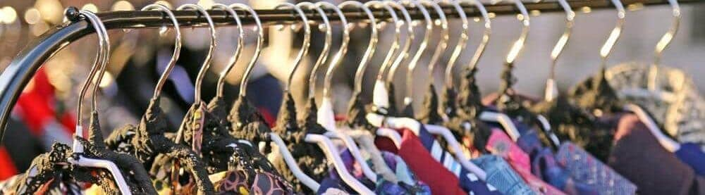 A close look at a rack of vintage clothes on display.