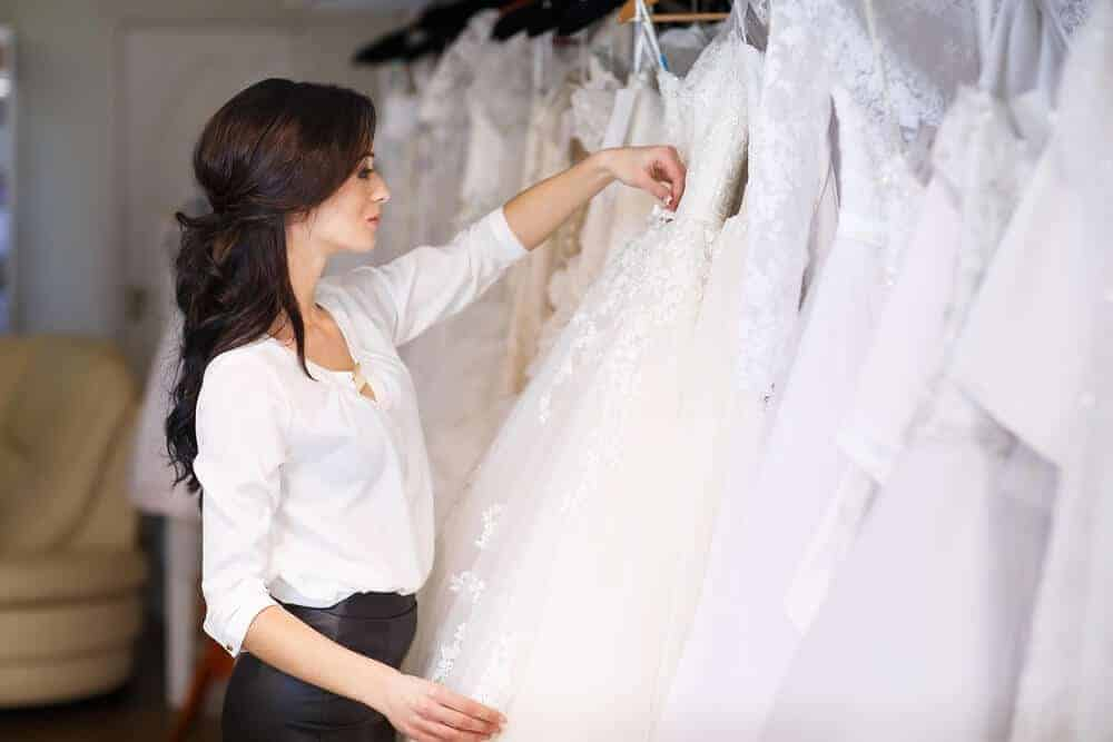 A woman browsing through the wedding dresses on display at a store.