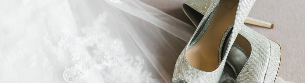 A close look at a wedding dress and a pair of shoes.