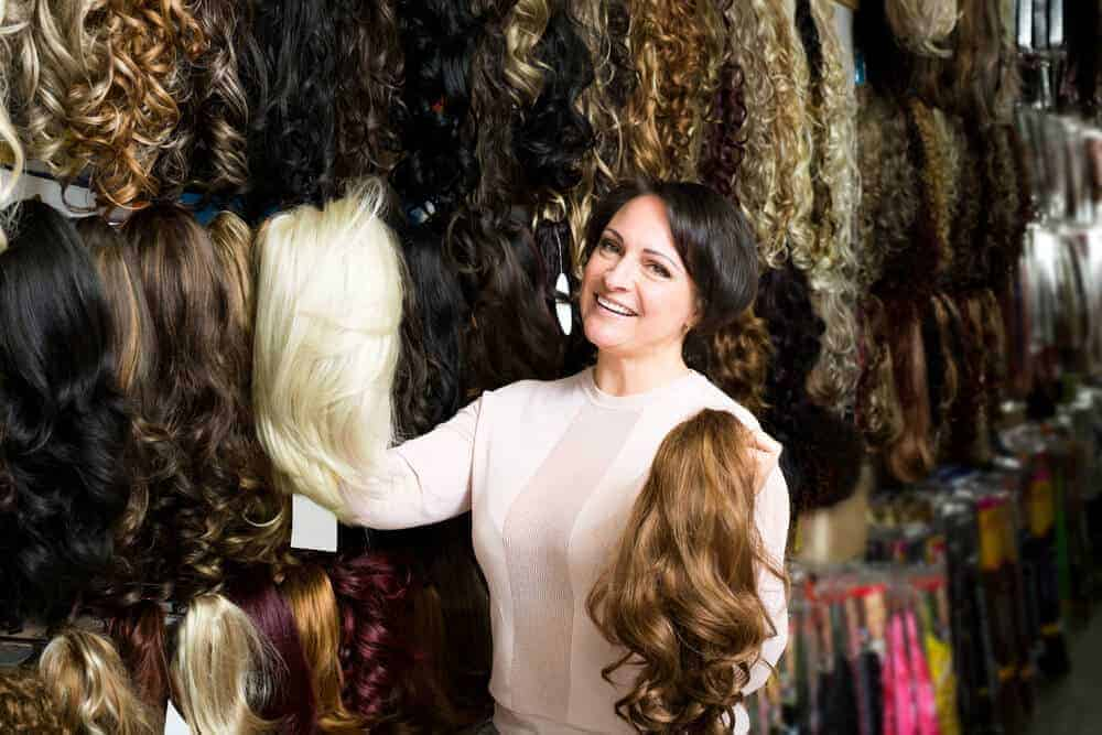 A woman browsing through the wigs on display at a store.