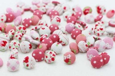 A bunch of pink floral cloth buttons.