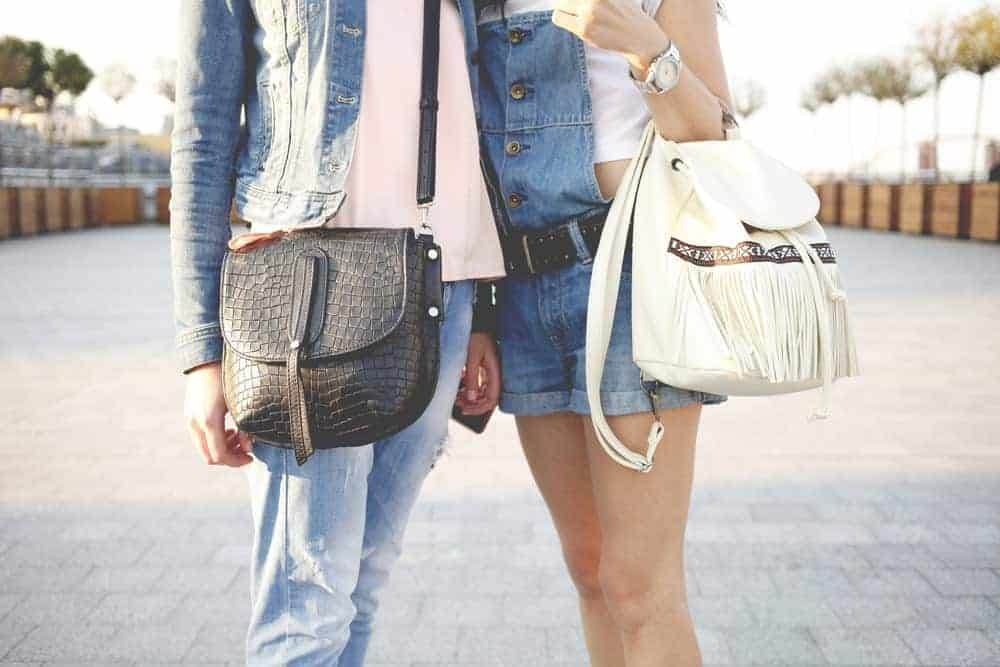 A close look at a couple of women carrying purses.