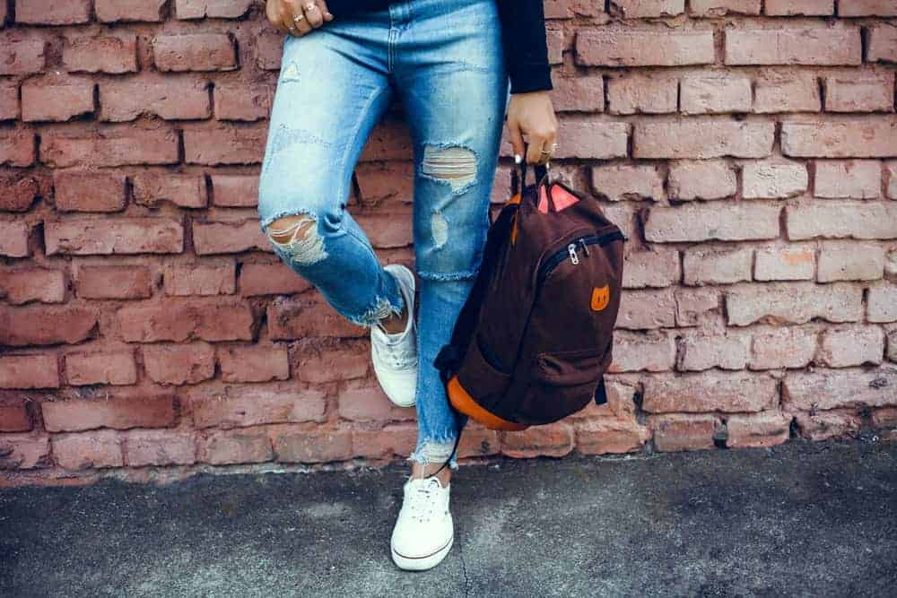 A person in tattered jeans and white sneakers clutching a backpack in one hand while leaning against a brick wall.