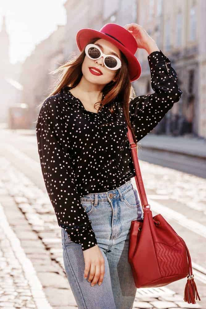 A woman wearing a hat, shades, and bucket bag..