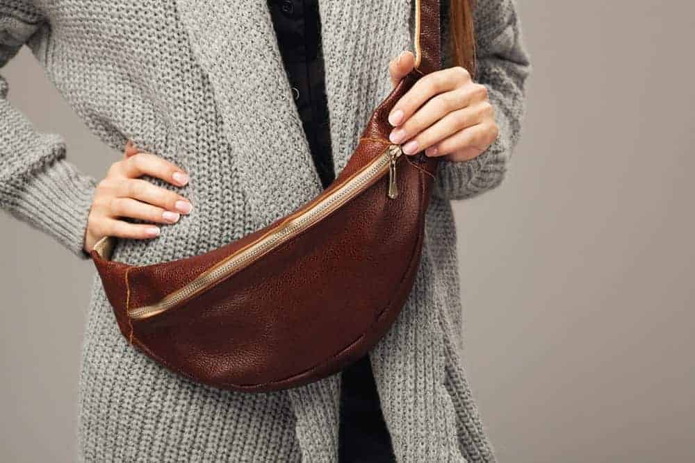 Closeup of a person wearing a leather fanny bag.