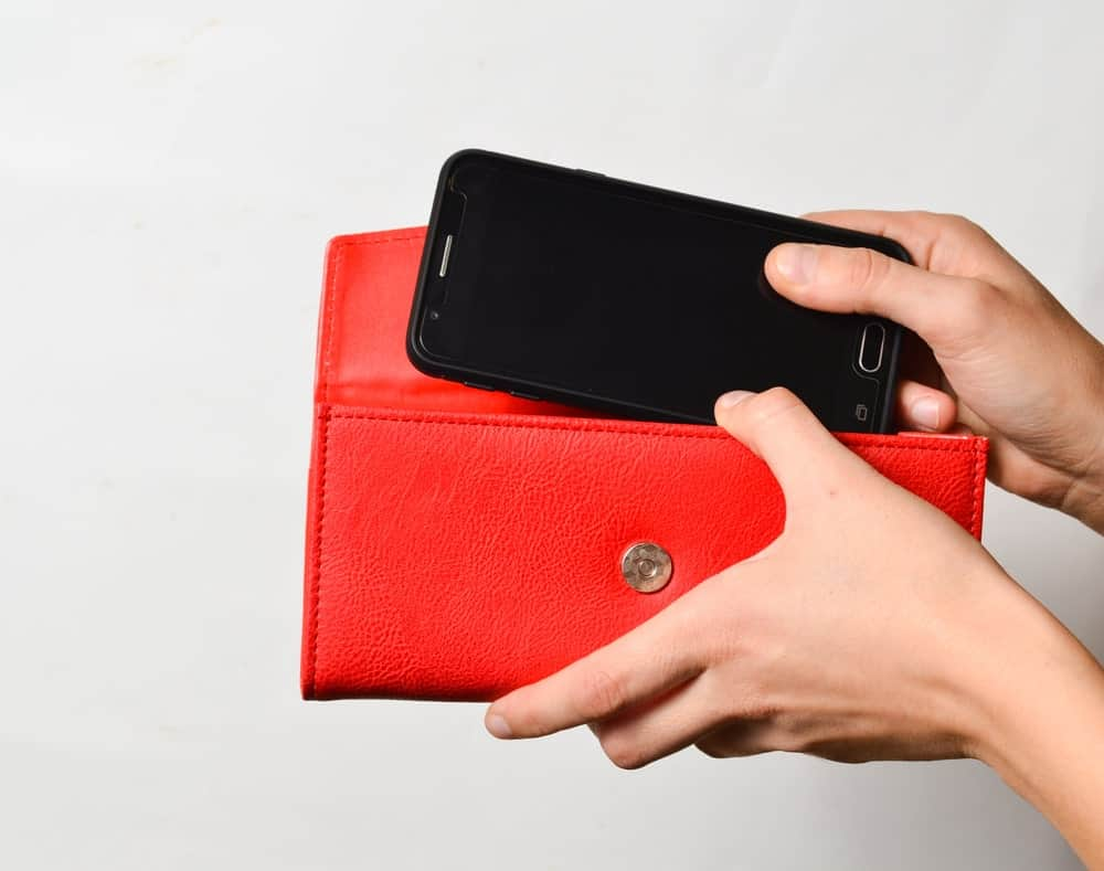 Hand holding a phone wallet and another placing a mobile phone inside.
