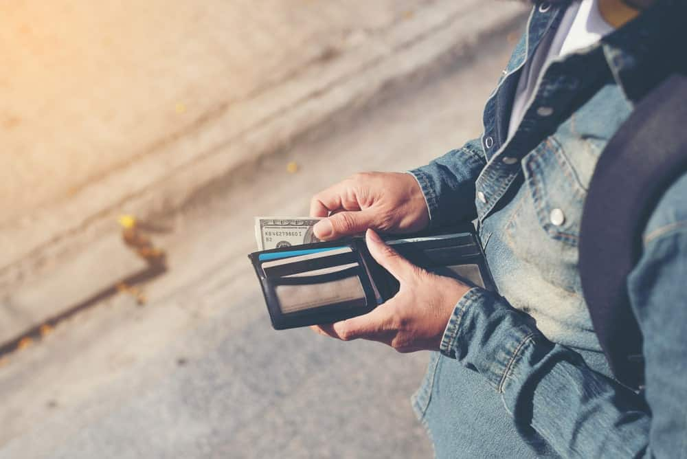 A person placing or pulling out paper bill from a wallet.