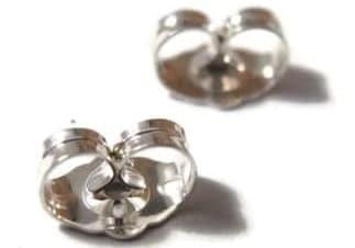 Silver earring backs on white background.