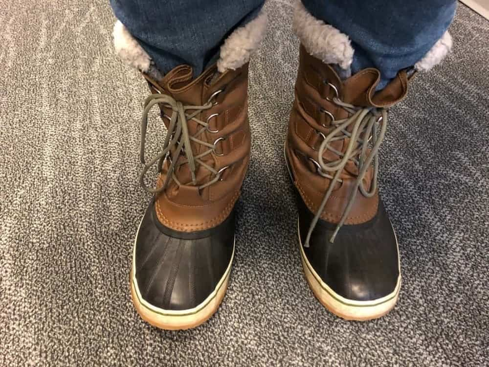Sorel Caribou boots laced up worn with jeans.