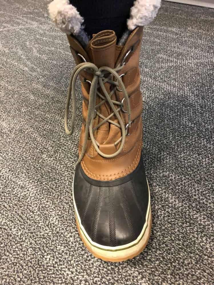 Close up photo of Sorel Caribou boots laced up with stainless steel lace loops.