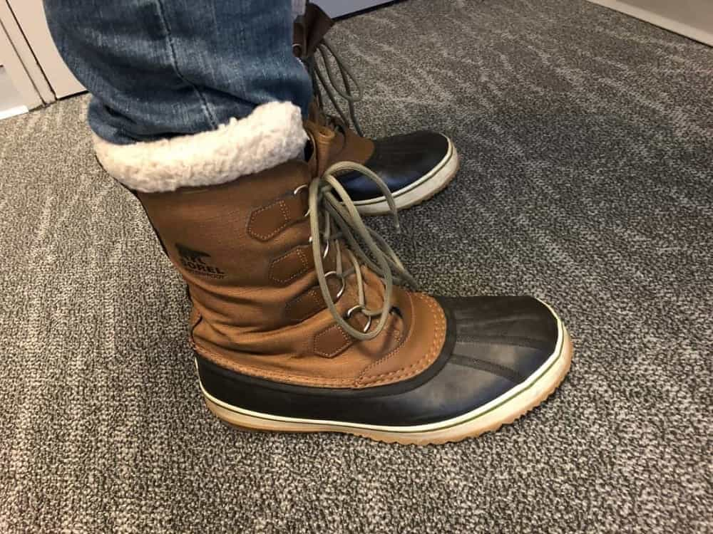 Side view of Sorel Caribou boots with jeans tucked inside.