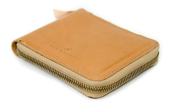 A small, zippered wallet in Tan.
