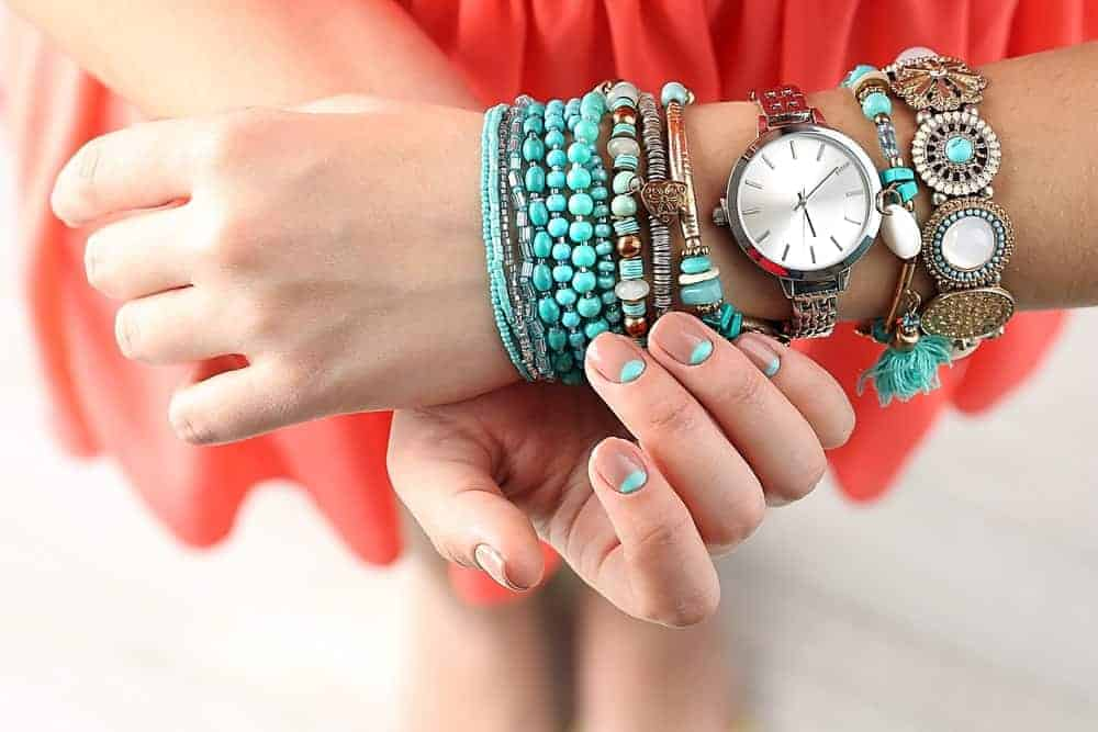 A look at a woman's wrist wearing different types of bracelets.