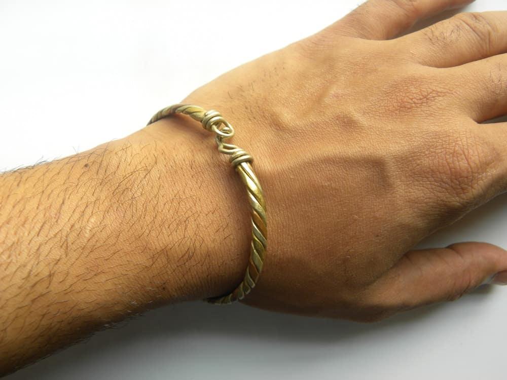 A close look at a man's hand wearing a Kada bracelet.