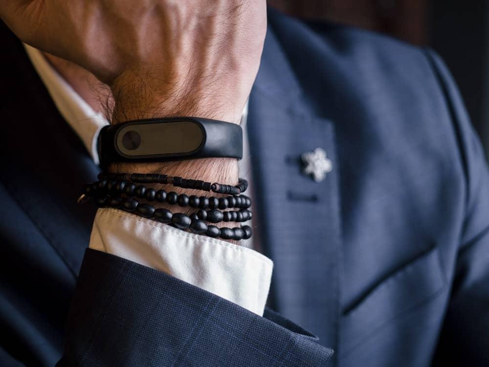 A man is wearing a sports bracelet at work.