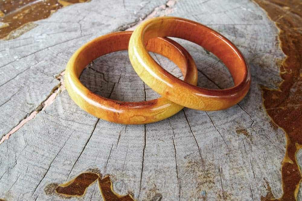 A couple of Wooden bracelets on a tree stump.