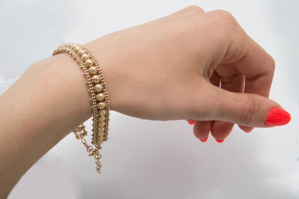 A close look at a woman's wrist wearing a Gold bracelet.