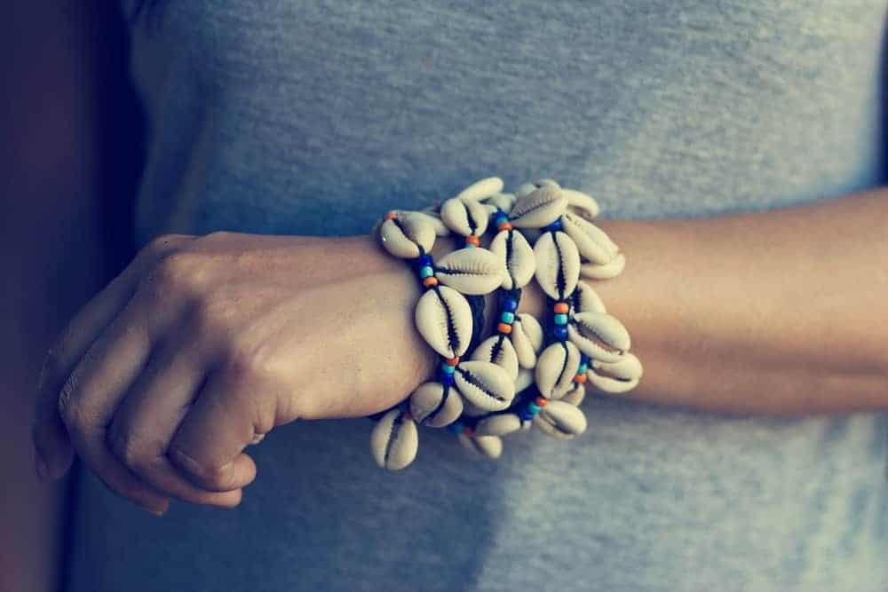 A woman wearing a set of shell bracelets.
