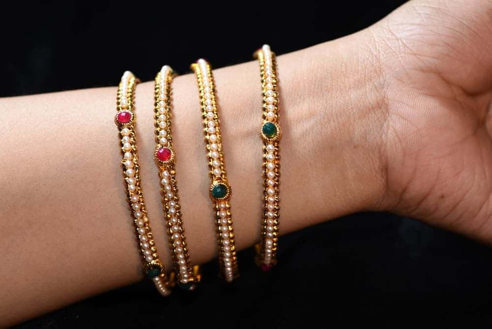 A lady is wearing four bangle bracelets of the same type.