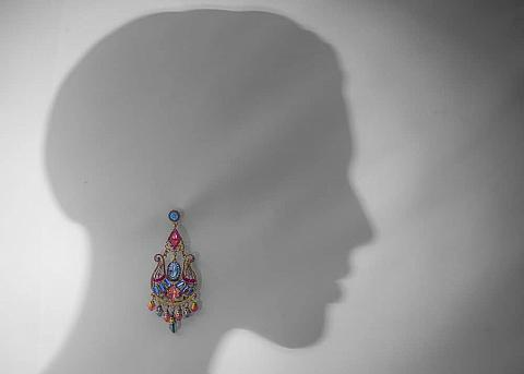 A silhouette of a woman with a colorful earring on it.