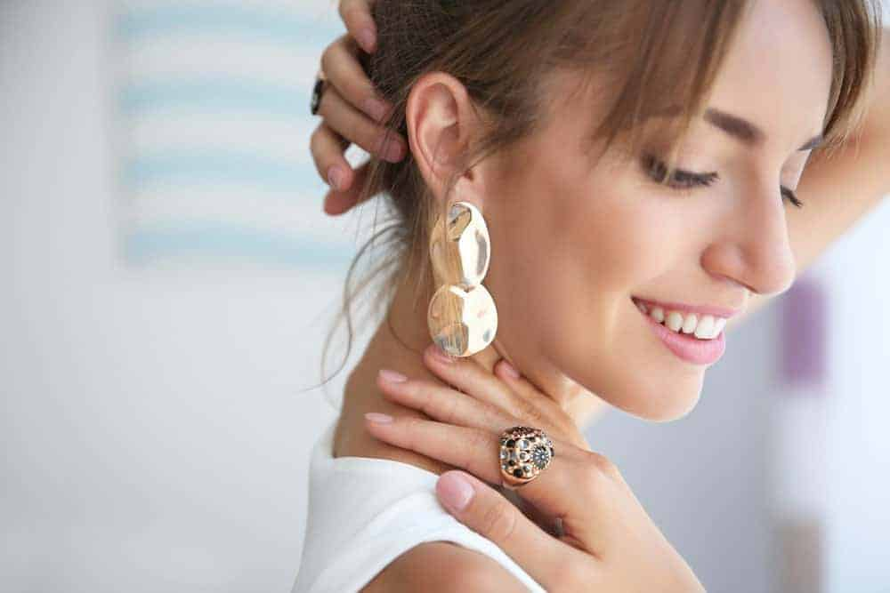 Woman showing off her pendant earring.