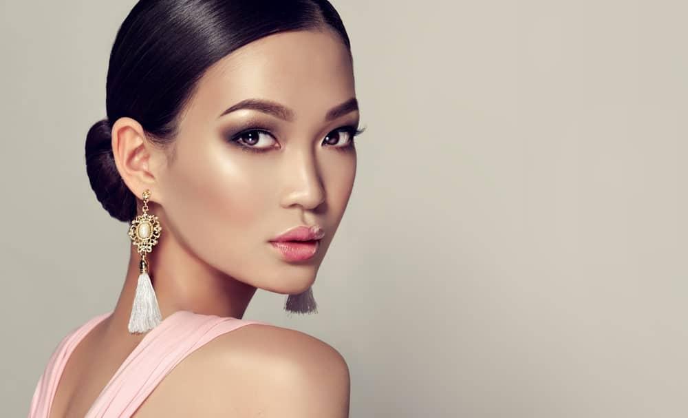 Asian model with dangling earrings.