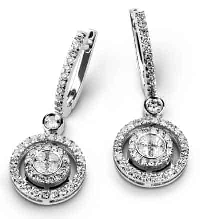 A pair of studded silver earrings with clip earring backs on white background.