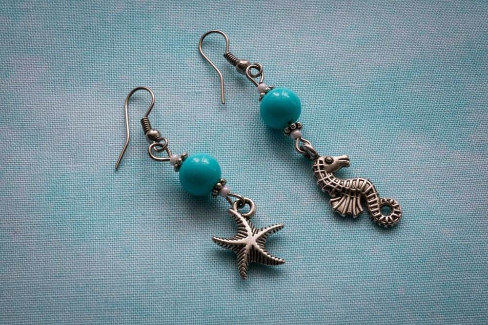 A pair of dangling earrings with French wire backs on a blue textile background.