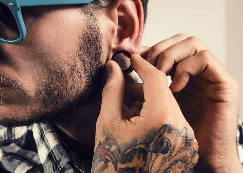 Bearded man with shades and tattoed hands putting on a gauge earring.