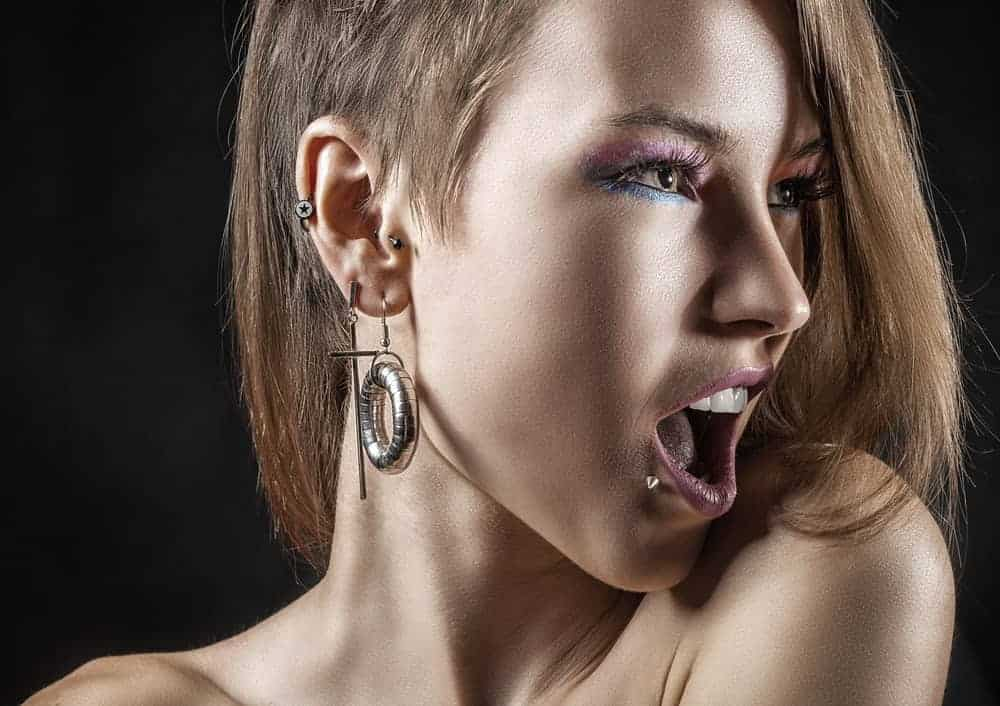 Woman with different ear piercings and another just beside her lower lip.