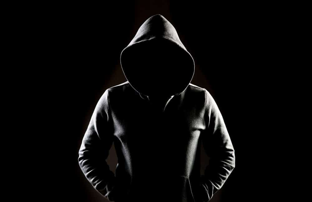 The dark outline of a man wearing a hoodie in the shadows.